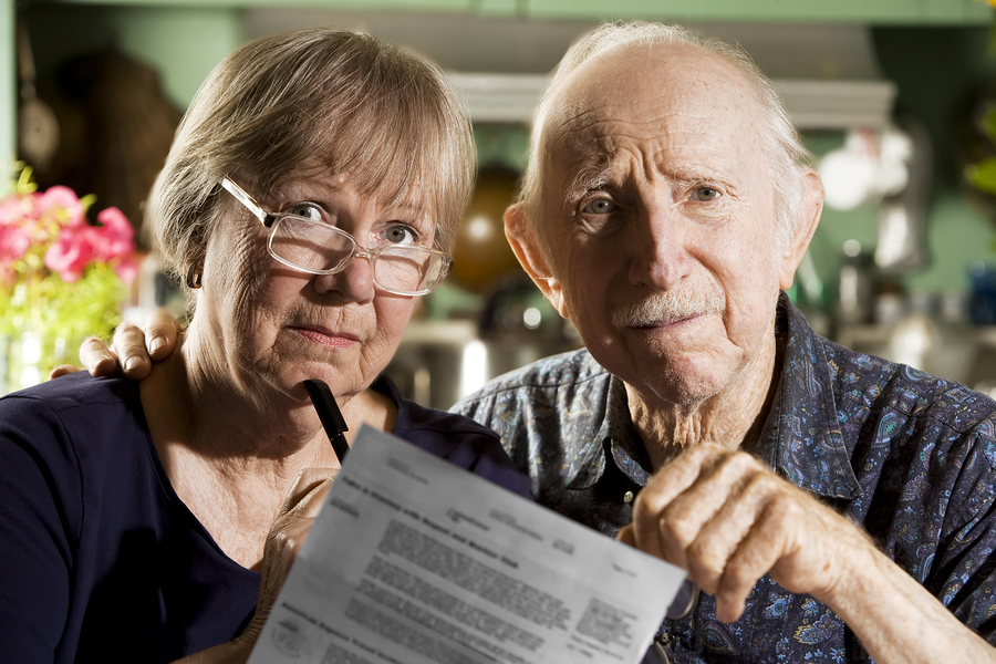 Senior couple reviewing paperwork with reservation