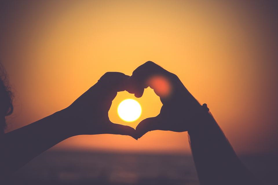 Hands in heart shape around setting sun