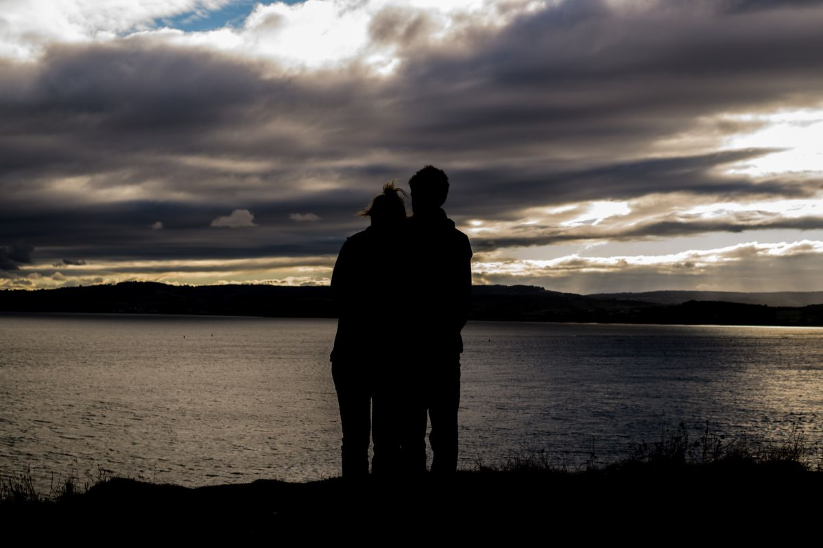 Photo of couple standing at the edge of a lake