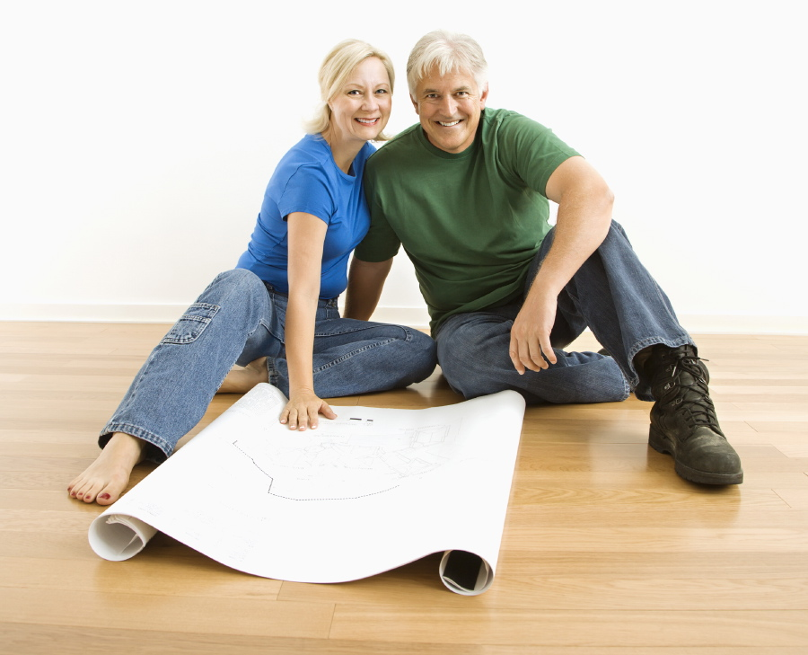 Photo of middle-aged couple sitting on floor with architectural blueprints