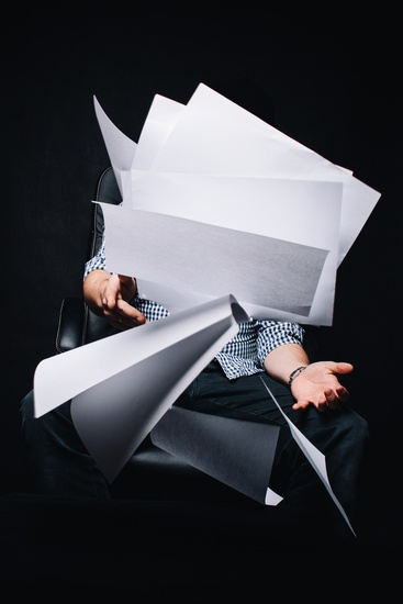 Photo of person throwing blank sheets of paper