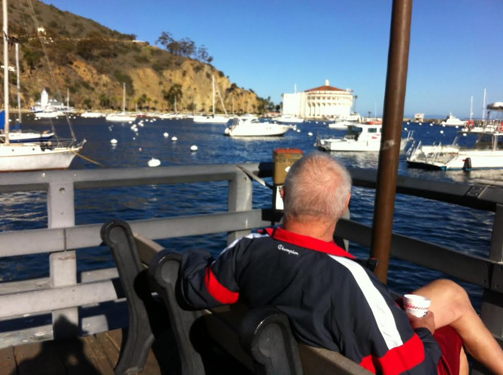 Sporty senior man with coffee on bench looking out over marina