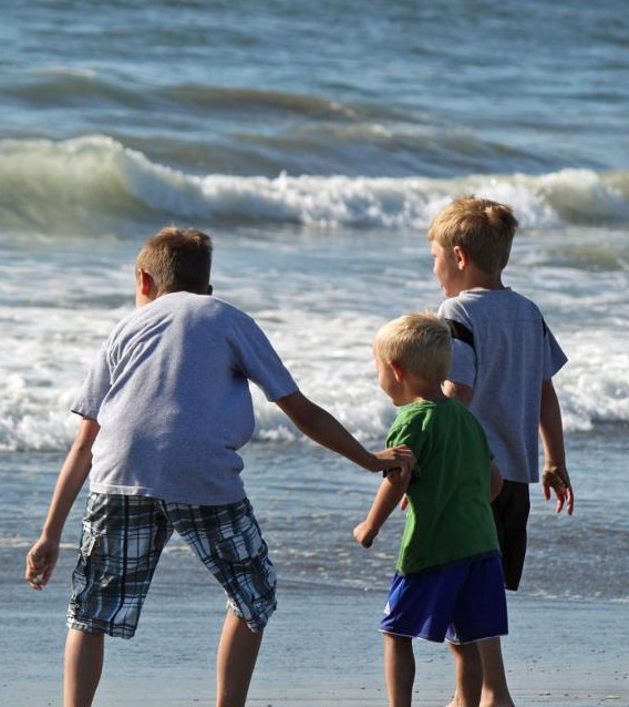 Three children playing in ocean waves