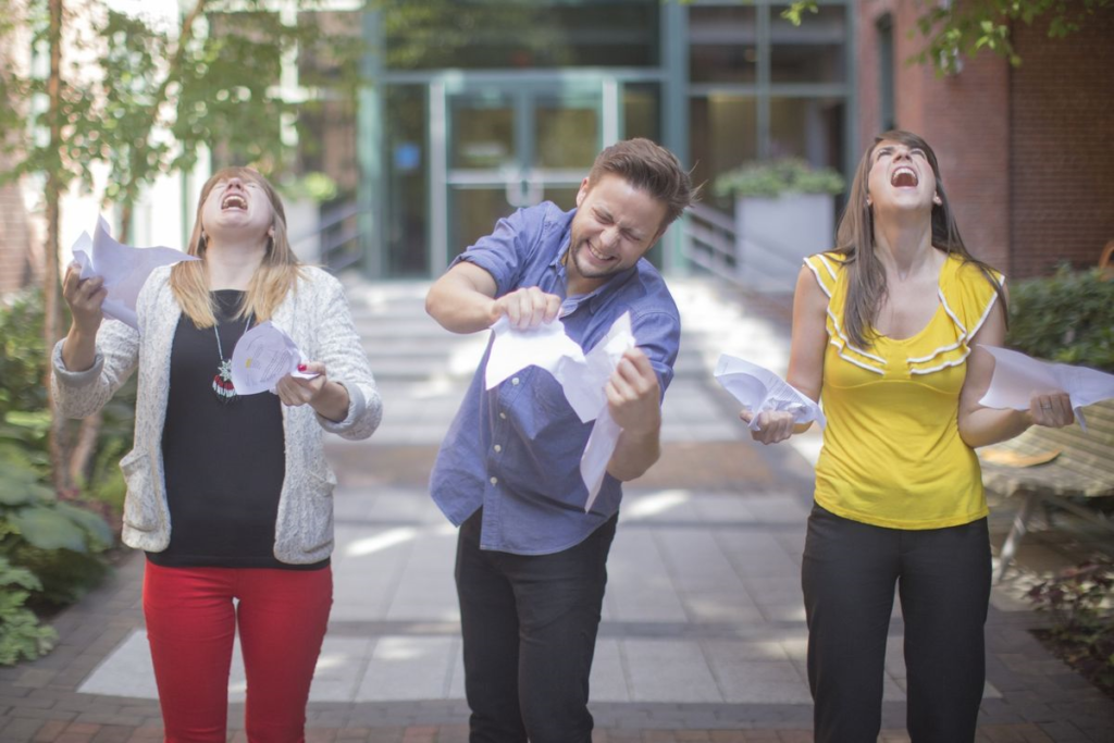 Three people ripping paper up