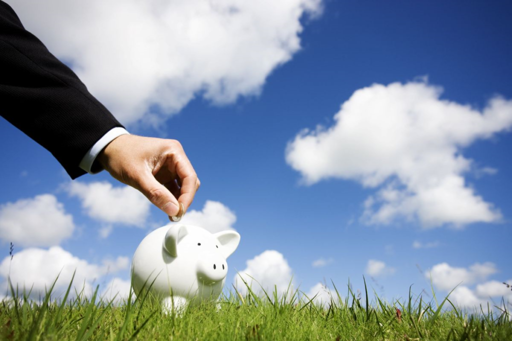 Male hand placing coin in piggybank with blue sky, clouds, and grass