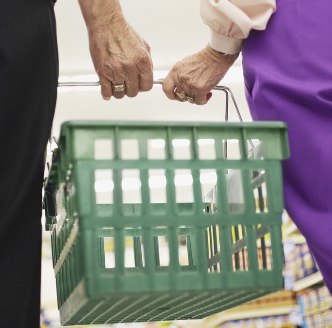 Photo of couple holding shopping basket in grocery store