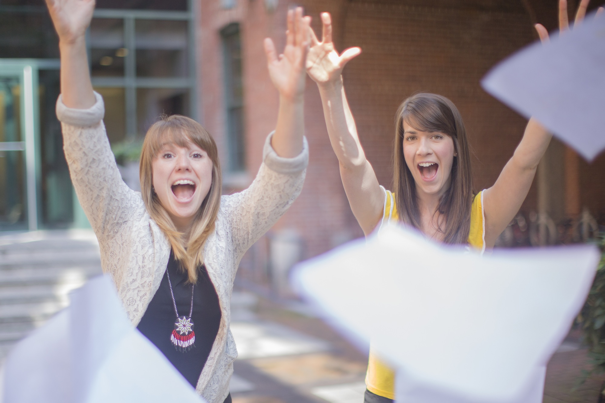 Photo of two young women throwing paper