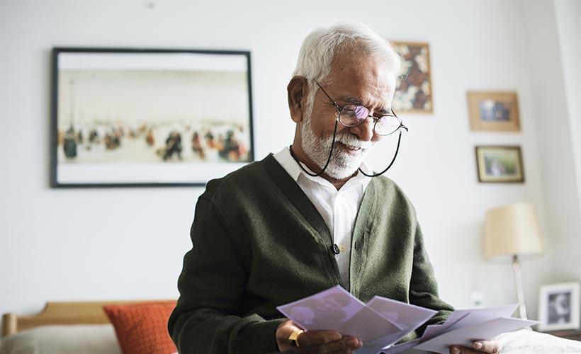 Senior man holding family photos